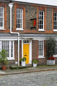 Old English house with brick wall and yellow door